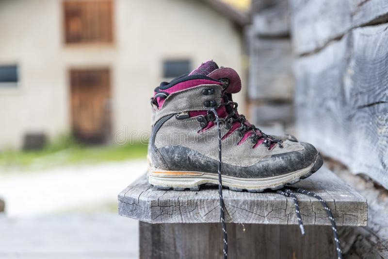 Trekking boots on the veranda of an alpine hut. Summer holidays in the mountains. Close up picture of hiking boots on a rustic wooden veranda of an alpine hut stock image