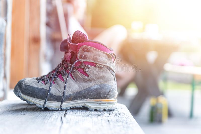 Trekking boots on the veranda of an alpine hut. Summer holidays in the mountains. Close up picture of hiking boots on a rustic wooden veranda of an alpine hut royalty free stock image