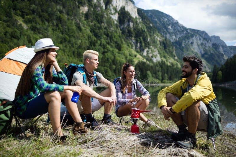 Trekking, campa, fotvandra och lös livbegrepp Gruppen av vänner fotvandrar i natur arkivfoto