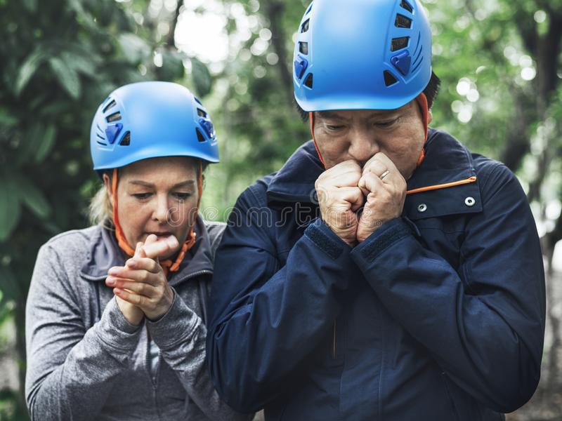 Trekking couple warming their hands royalty free stock photo
