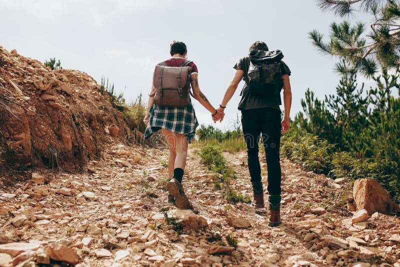 Trekking de couples d'explorateur une colline images libres de droits