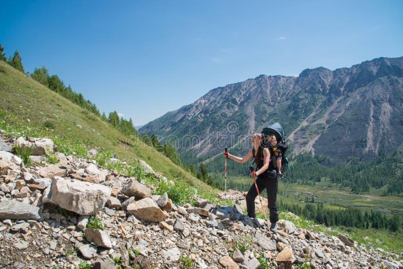 Trekking de randonneur de femme en montagnes avec l'enfant dans le sac à dos Mère avec le bébé garçon voyageant dans le jour enso photo libre de droits