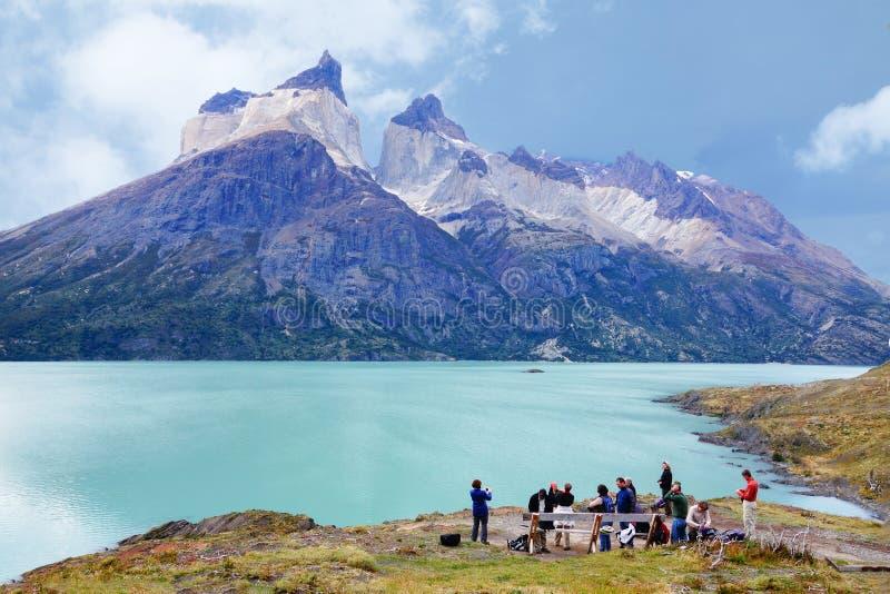 Trekking de touristes pour voir des klaxons de Paine et de beau lac dans le massif de roche photo stock