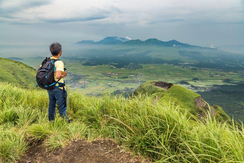 Trekking della viandante alla cima della collina ed al vulcano di sorveglianza del Monte Aso fotografie stock