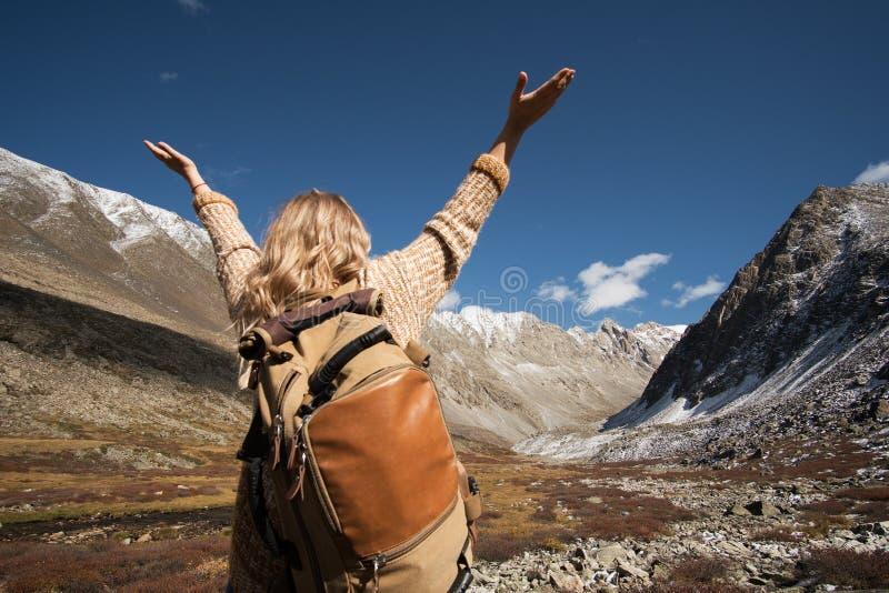 Trekking di viaggiatore con zaino e sacco a pelo della donna in montagne selvagge fotografia stock