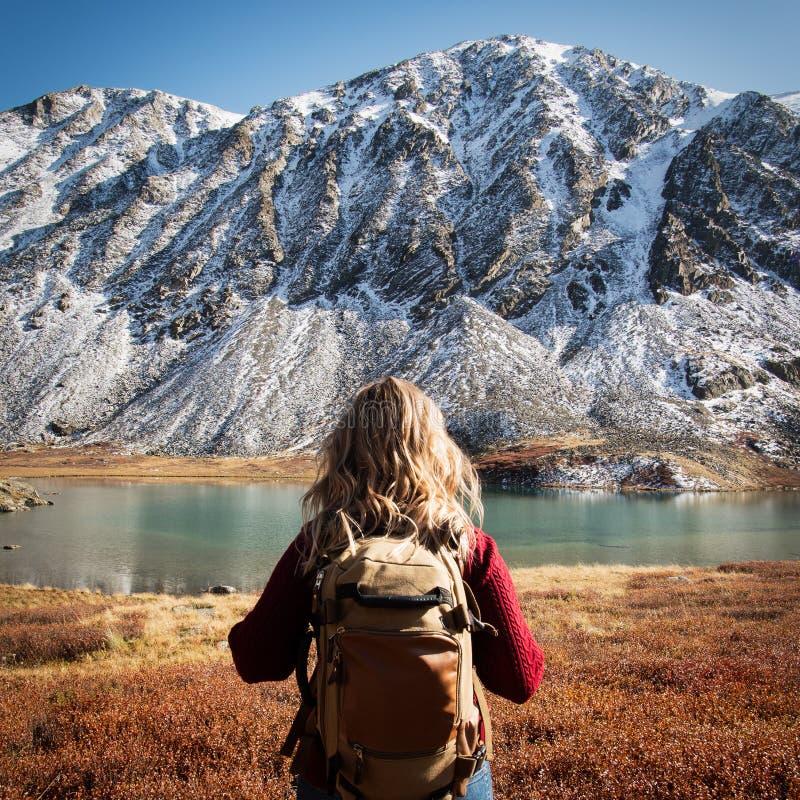 Trekking di viaggiatore con zaino e sacco a pelo della donna in montagne selvagge fotografie stock