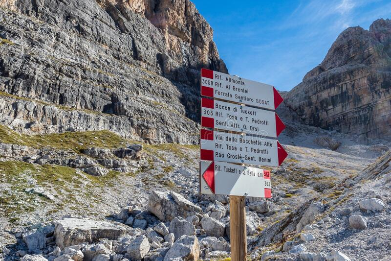 Trekking direction indicators. Tourist paths directions and travel time shown on a traditional direction signs at the Dolomiti stock photo