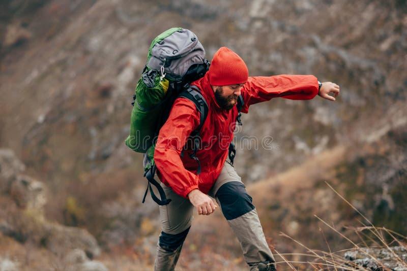 Trekking ed alpinismo maschii barbuti del viaggiatore durante il suo viaggio Giovane estremo che fa un'escursione in montagne immagine stock