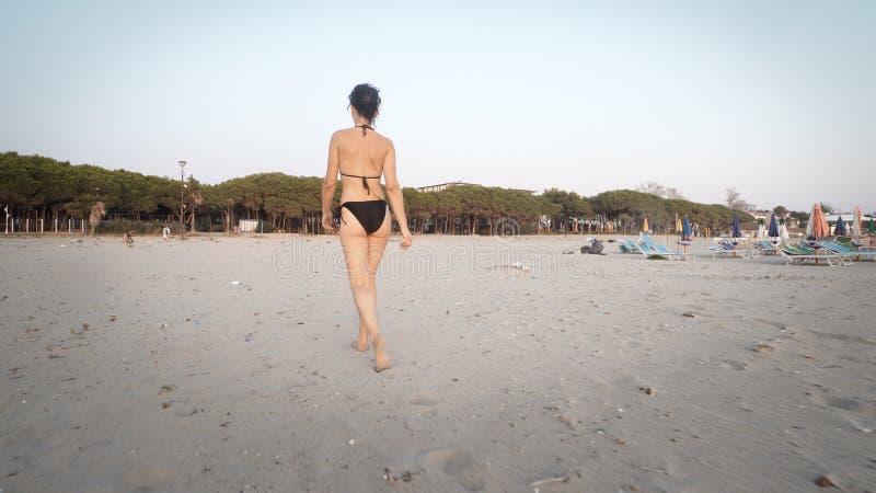 Trekking en kvinnlig modell för mode i bikini gå på den tomma stranden royaltyfria bilder