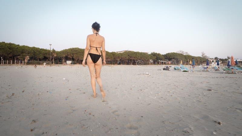 Trekking en kvinnlig modell för mode i bikini gå på den tomma stranden fotografering för bildbyråer