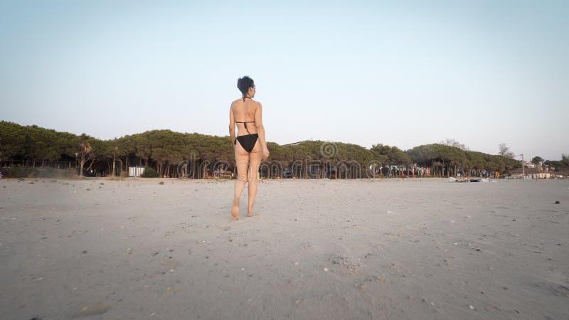 Trekking en kvinnlig modell för mode i bikini gå på stranden arkivfoto