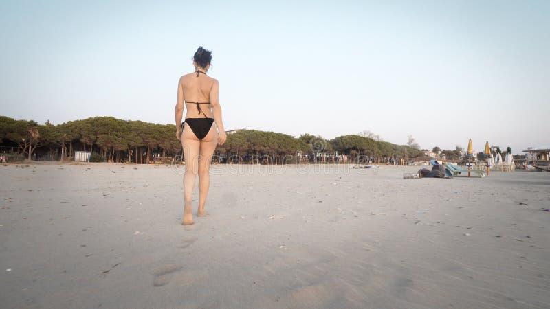 Trekking en kvinnlig modell för mode i bikini gå på tom strandsand på soluppgång royaltyfri foto