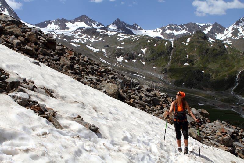 Trekking fotvandra för flicka i fjällängarna, Stubai, Österrike royaltyfri bild