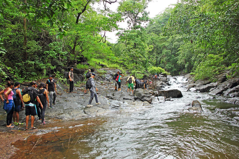 Trekking in Goa during Monsoon. Goa, India - September 18, 2016: Group of enthusiasts trek along the rugged banks of Salaulim River in Netravali in Goa, during royalty free stock photos