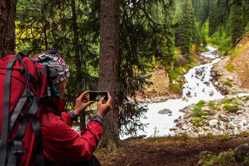 Trekking in the mountains. Girl takes a photo a landscape with a river on a smartphone stock images