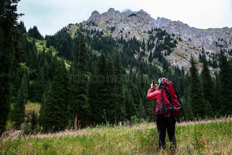 Trekking in the mountains. Girl takes a photo a landscape on a smartphone royalty free stock photos