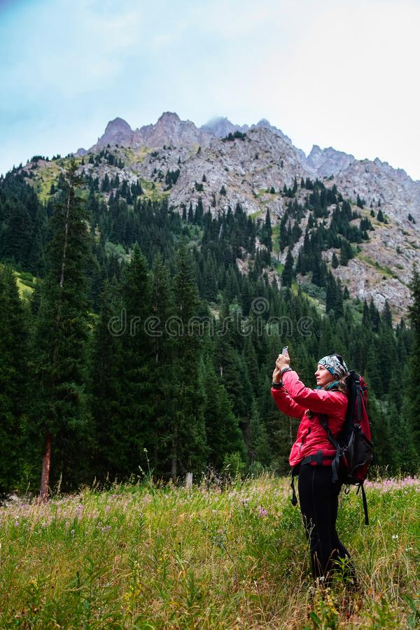 Trekking in the mountains. Girl takes a photo a landscape on a smartphone royalty free stock photo