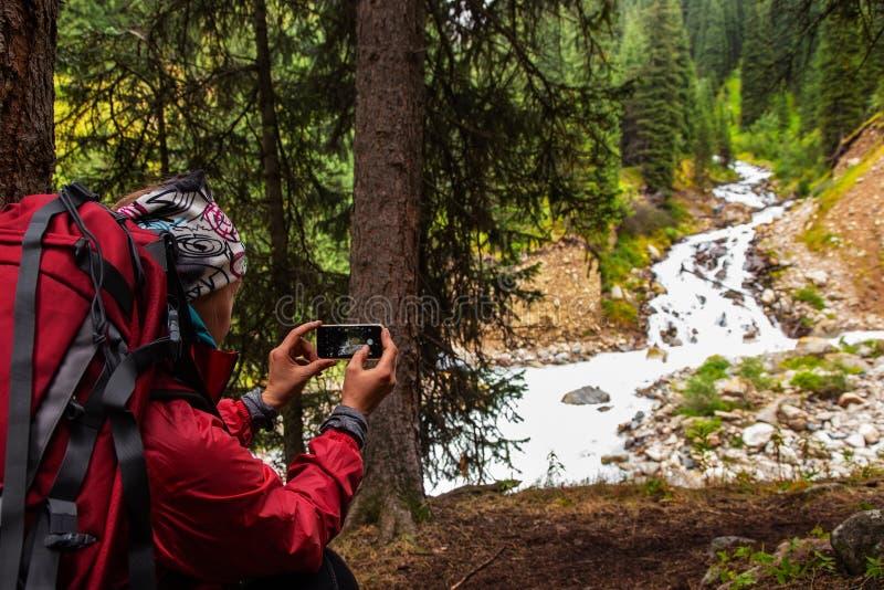 Trekking nas montanhas A menina toma a uma foto uma paisagem com um rio em um smartphone imagens de stock