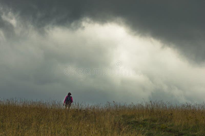 Trekking through prairie hillside under dark clouds. Of summer storm, central Serbia stock images