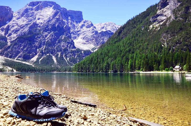 Trekking shoes at the mountain lake in italian alps royalty free stock photos