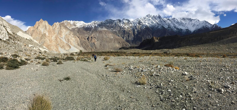 Trekking trail in Passu show drought landform, snow capped mountains in Karakoram range. stock images