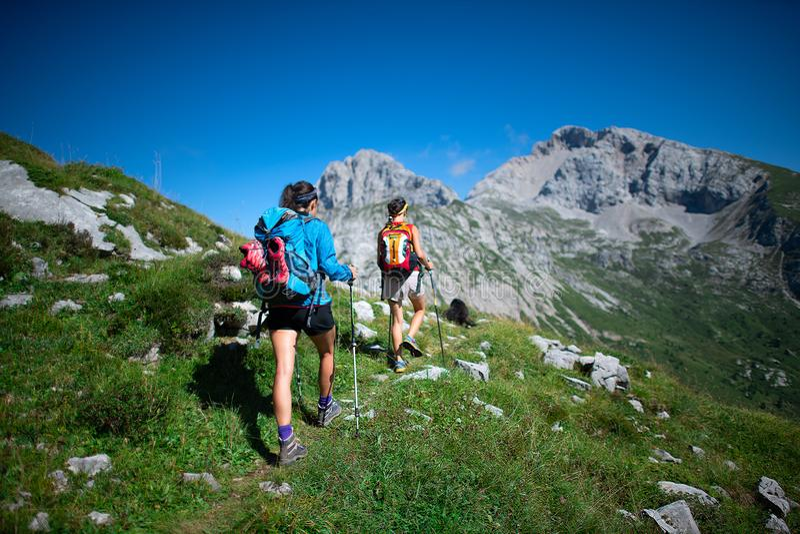Trekking van twee medewerkers die in de bergen op een dag weg werken royalty-vrije stock afbeelding