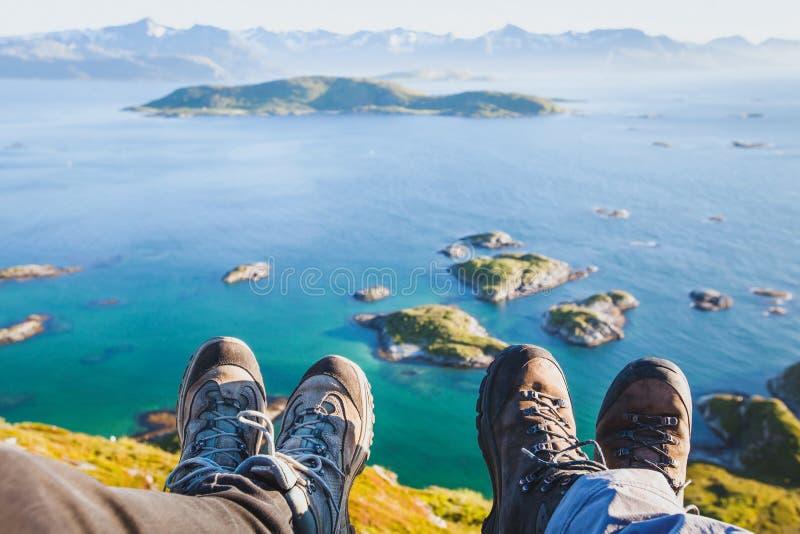 Trekkingsschoenen op voeten van paar van reizigerswandelaars die bovenop de berg zitten stock foto's