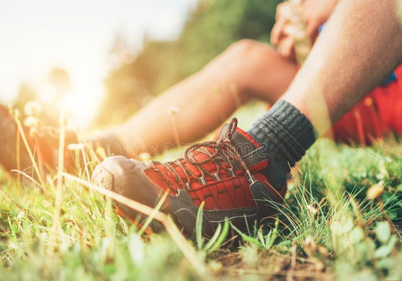 Trekkingstiefel von Backpacker in Nahaufnahme Der Mensch hat eine Ruhepause auf grünem Gras und genießt Bergwandern, Aktiv stockbilder