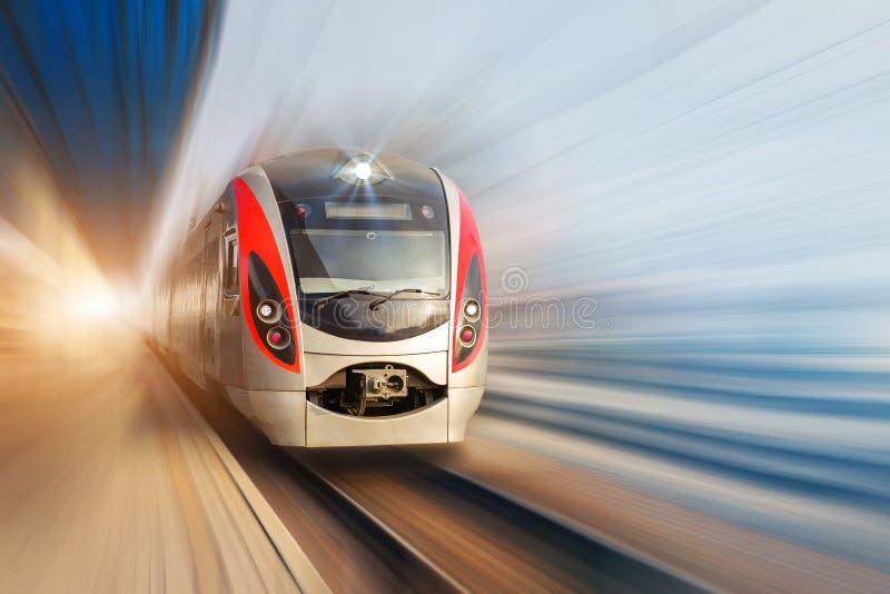 Trem bonde de alta velocidade do passageiro moderno que move-se rapidamente ao longo da plataforma terminal Borrão de movimento foto de stock