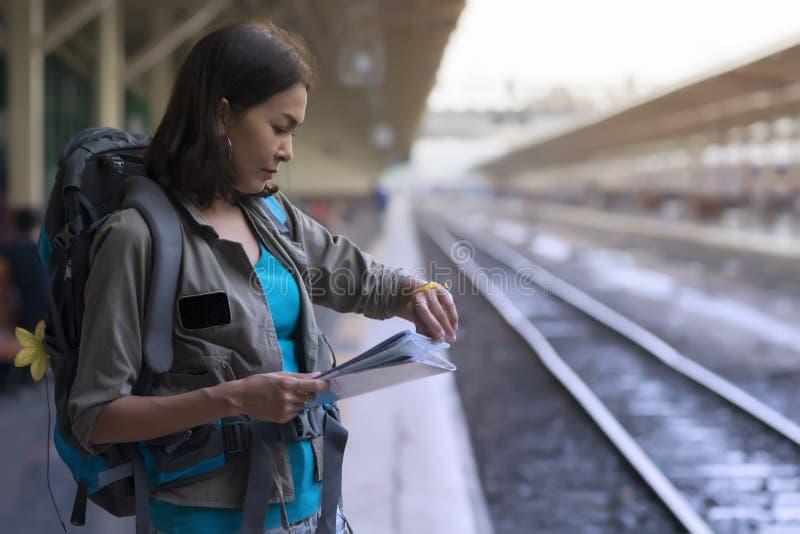 Trem da espera do suporte da mulher de Ásia pela viagem do viajante e o tempo da verificação fotos de stock royalty free