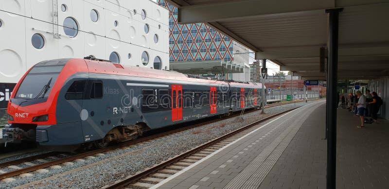 Trem da R-rede que espera na estação do Gouda para partir ao antro aan Rijn de Alphen com o cinama com furos do queijo na parte t imagens de stock