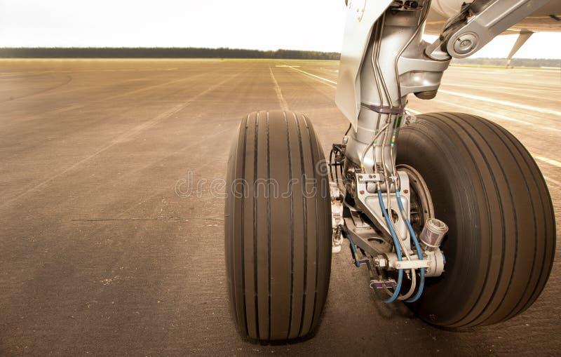 Trem de aterragem, rodas, na pista de decolagem, fim acima imagem de stock royalty free