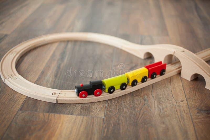 Trem de madeira do brinquedo na estrada de ferro com ponte de madeira Limpe o assoalho laminado foto de stock