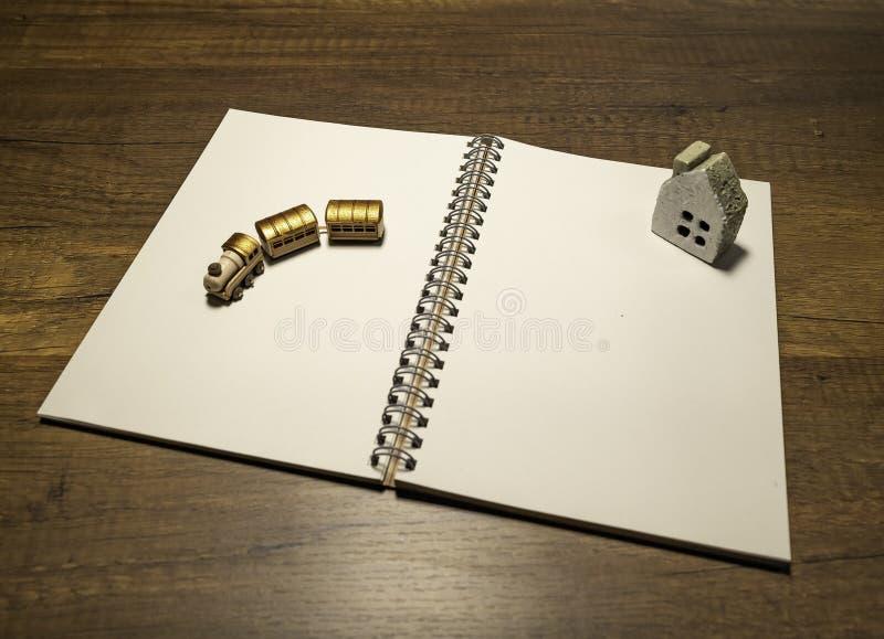Trem de madeira dourado e casa de pedra no caderno branco vazio imagens de stock