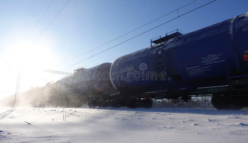 Trem de mercadorias com os tanques de óleo no movimento A poeira da neve voa de um trem de passagem na alta velocidade Dia ensola imagens de stock