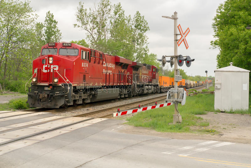 Trem de mercadorias no cruzamento de estrada imagens de stock