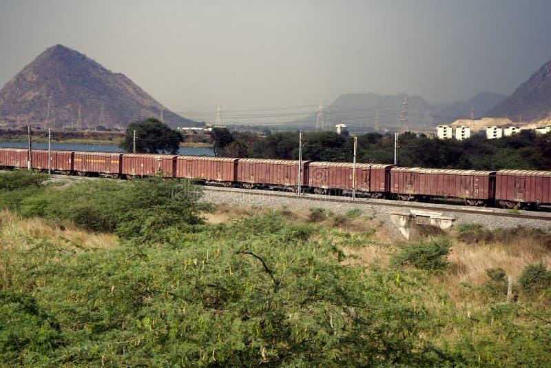 Trem de mercadorias no fundo do campo indiano pitoresco foto de stock