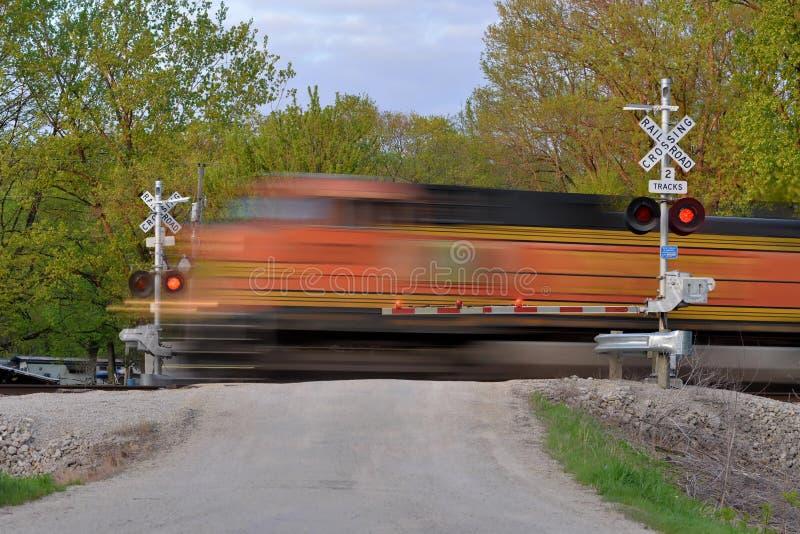 Trem de mercadorias no movimento na porta de cruzamento imagens de stock royalty free