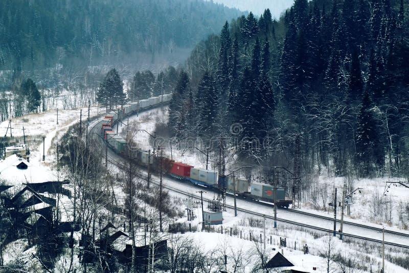 trem de mercadorias que move-se através da floresta conífera durante a queda de neve foto de stock