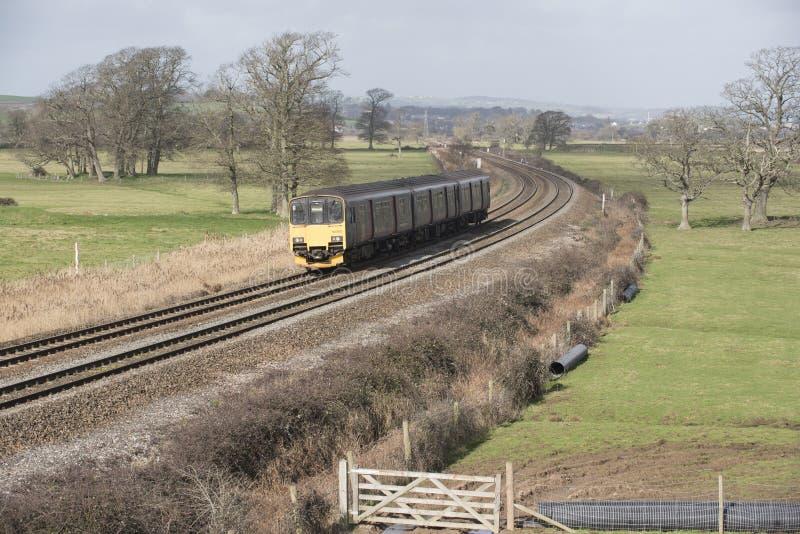 Trem de passageiros uma terraplenagem em Devon Reino Unido fotografia de stock