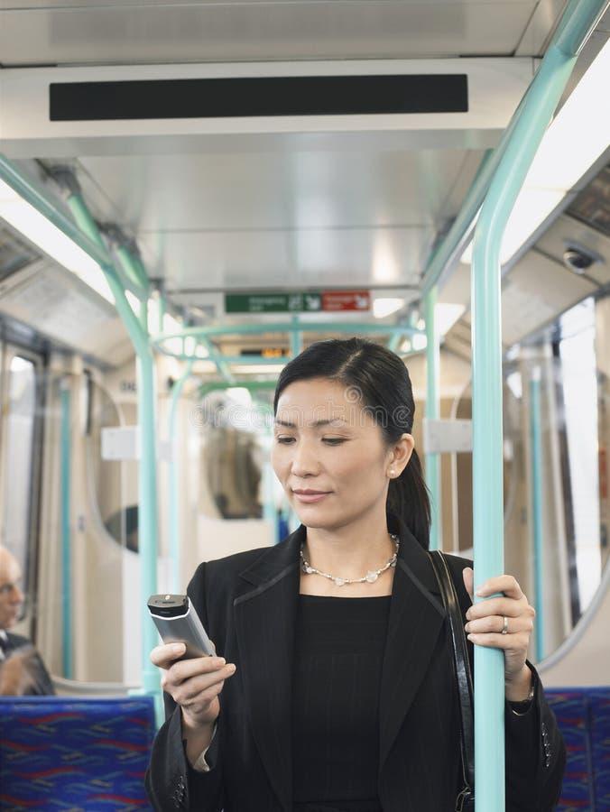 Trem de Using Cellphone In da mulher de negócios fotografia de stock