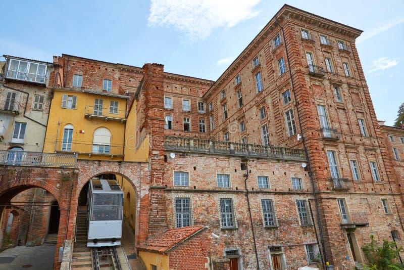 Trem do teleférico e construções de tijolos antigas em um dia de verão ensolarado em Mondovi, Itália fotos de stock royalty free