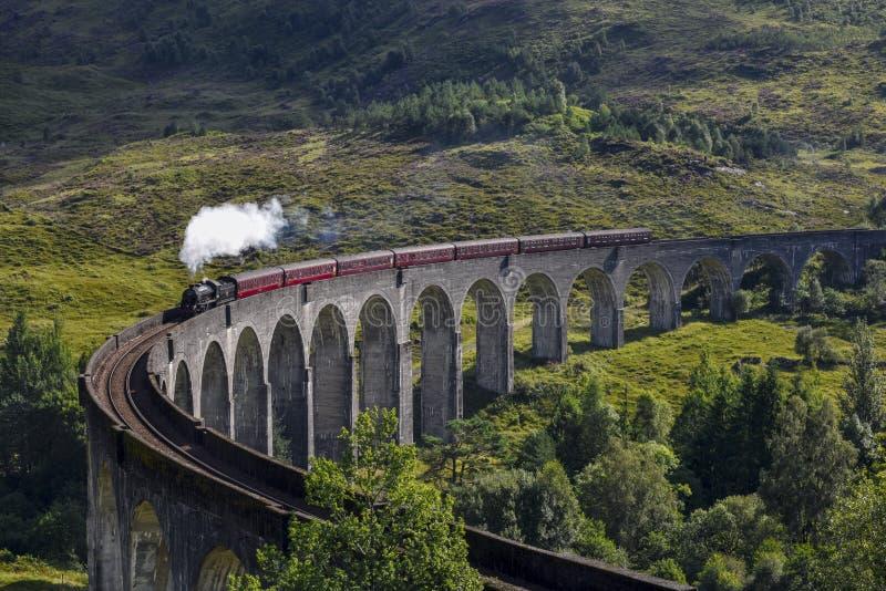 Trem do vapor de Jacobite no viaduto que aproxima-se, montanhas de Glenfinnan, Escócia, Reino Unido imagem de stock