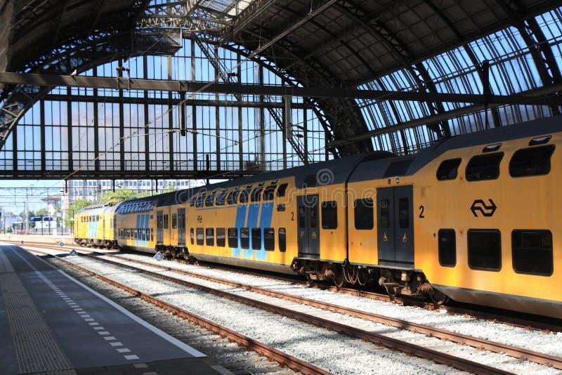 Trem dobro da plataforma que sae da estação de Amsterdão fotos de stock