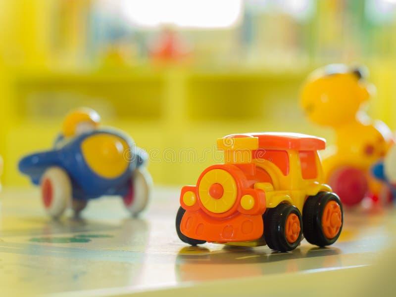 Trem e anither plásticos alaranjados do motor do brinquedo em uma tabela fotos de stock royalty free
