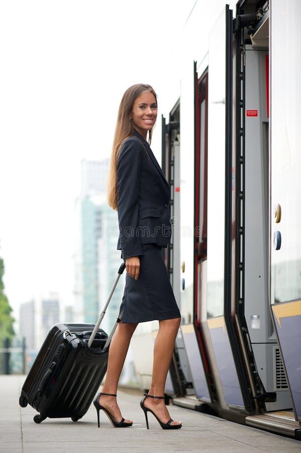Trem entrando da mulher de negócios com mala de viagem fotos de stock royalty free