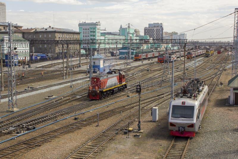 Trem moderno e velho na estação de trem no fundo das construções e de trilhas de estrada de ferro vazias imagem de stock
