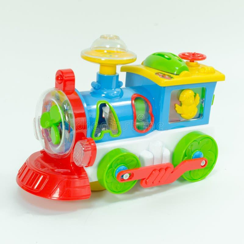 Trem plástico do brinquedo isolado no fundo branco Locomotiva plástica do brinquedo das crianças com letras do Abs imagem de stock royalty free