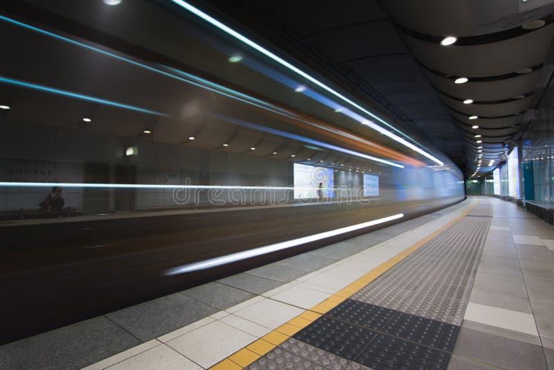 Trem rápido que viaja através da estação de metro subterrânea fotografia de stock