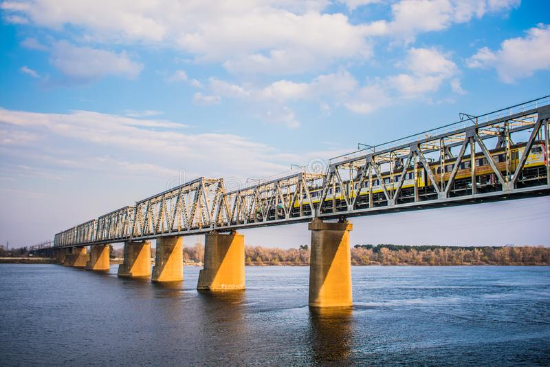 trem sobre a ponte do rio no tempo ensolarado fotografia de stock